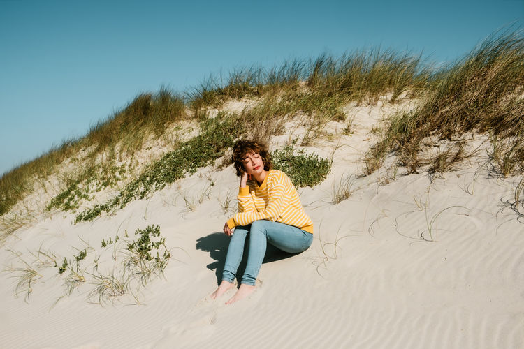 Full length of woman sitting on sand