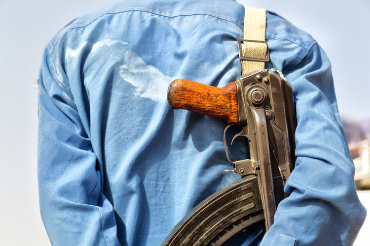 Midsection of man with rifle outdoors