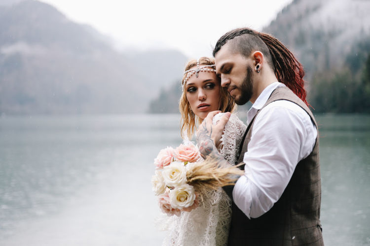 A loving married couple the bride and groom in suits celebrate wedding near the mountains and water