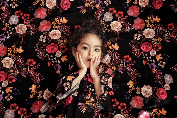 Portrait of cute girl against floral curtain