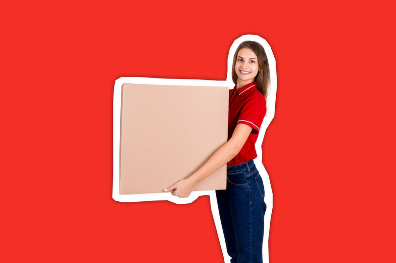 Portrait of a smiling young woman standing against red background