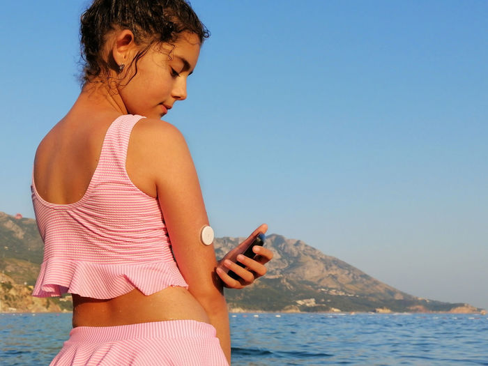 girl reads glucose level  from the white sensor on arm with cgm device before enters the sea.