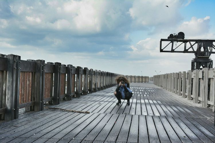 Woman Photographing While Crouching On Boardwalk