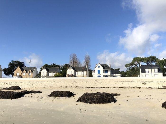 Houses on beach by buildings against blue sky
