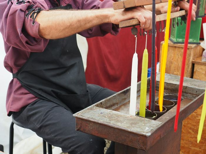 Midsection of man making candles while sitting on chair