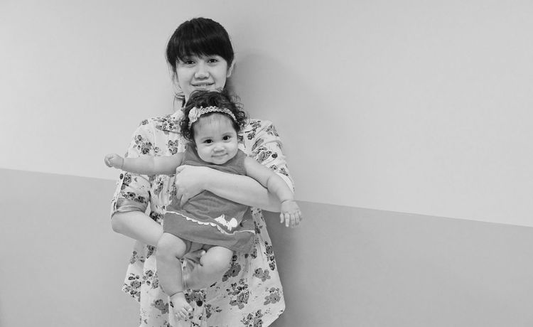 Baby Black And White Childhood Gray Background Mother Daughter  Portrait Standing Carrying Baby Smiling Looking At Camera Rule Of Thirds Curly Hair Cute