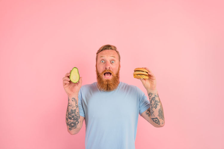 Midsection of man holding ice cream against gray background