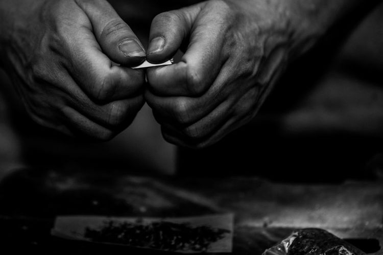 Cropped hands of man making marijuana joint on floor