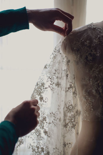 Cropped hands of female fashion designer with wedding dress on mannequin