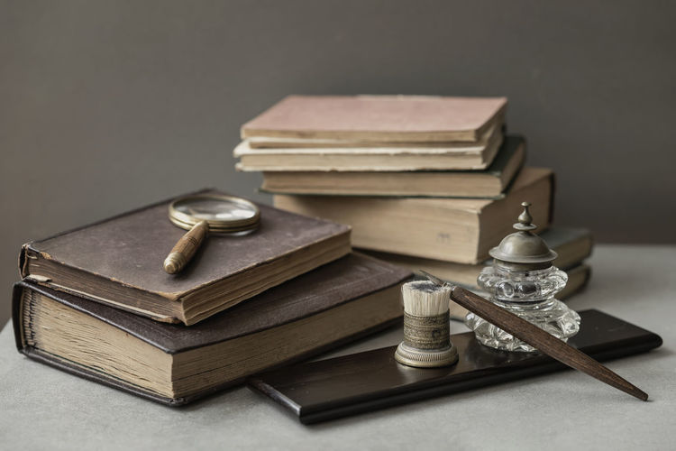 Several of antic books, set of old stationery, wooden pen, inkwell, magnifier close-up on desk, vintage background. Concept of reading and education, memory and nostalgy Still Life Stack Table No People Book Close-up Antique Old Hardcover Book Ink Well Vintage Magnifier Memory Nostalgia Archival Literature Retro Styled School Poetry Novel