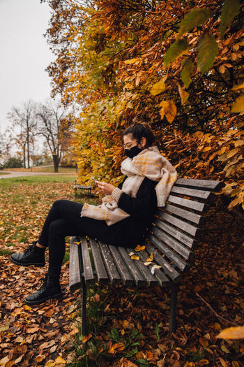 Young woman sitting on bench in park during autumn