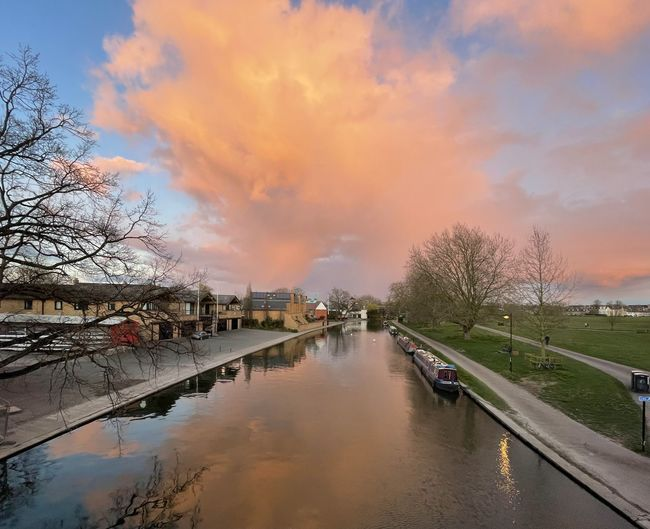 Canal amidst city against sky during sunset