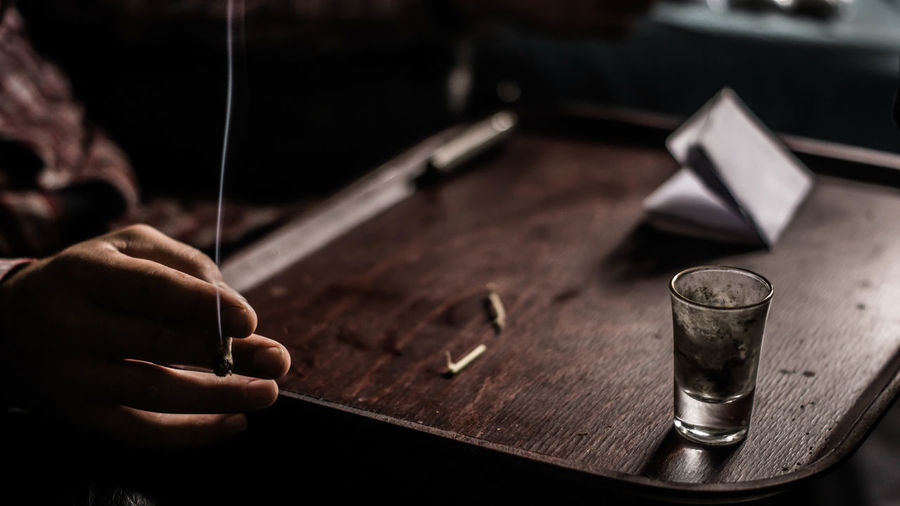Cropped Image Of Man Holding Cigarette At Table