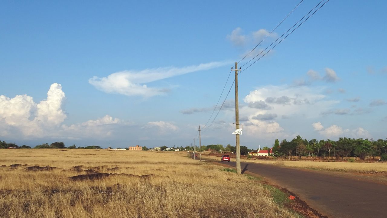 sky, cloud - sky, transportation, land, landscape, field, nature, environment, road, electricity, day, no people, technology, plant, fuel and power generation, cable, electricity pylon, grass, connection, beauty in nature, outdoors, power supply, telephone line