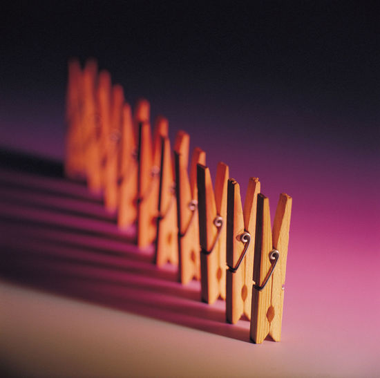 Close-Up Of Clothespins Against Colored Background