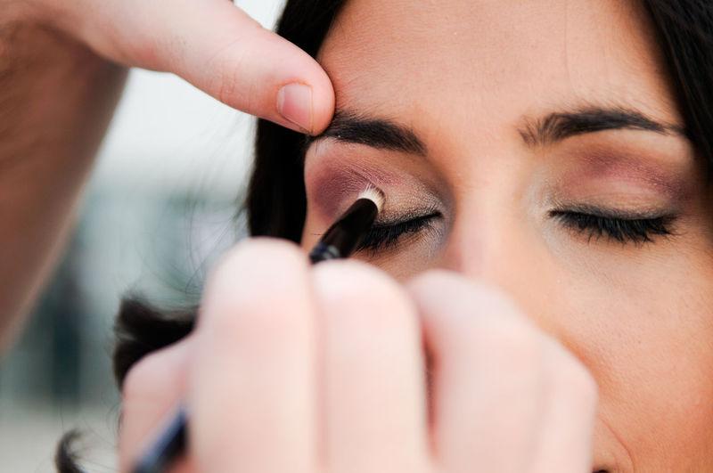 Woman Applying Eyeshadow On Friend Eye