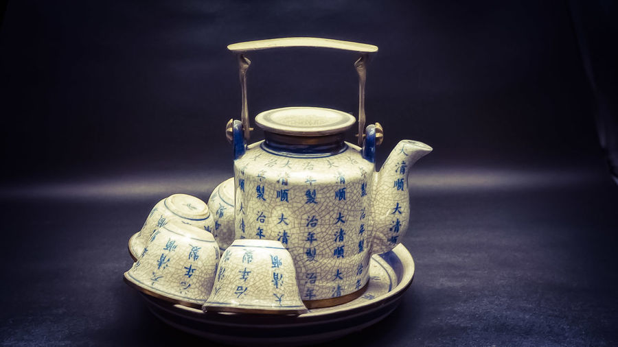 Close-Up Of Teapot And Cups In Plate On Table