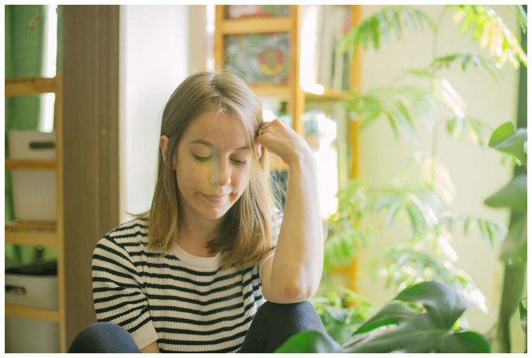 Portrait of young woman sitting at home