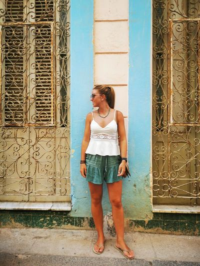 Full length of young woman standing against door