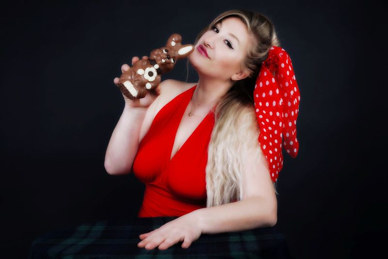 Portrait Of Woman Holding Toy Against Black Background