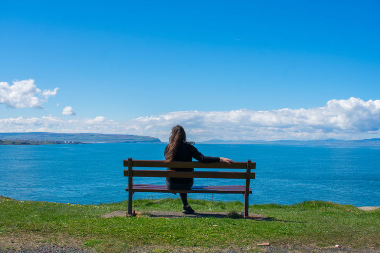 Rear View Of Woman Sitting On Bench While Looking At Sea Against Blue Sky