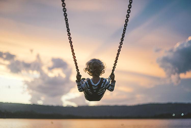 Boy on swing against sky