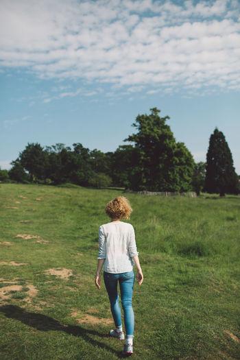 Rear view of mid adult woman walking on grassy field