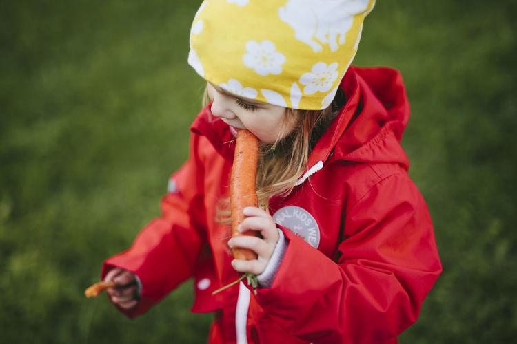 Full length of cute girl holding red umbrella