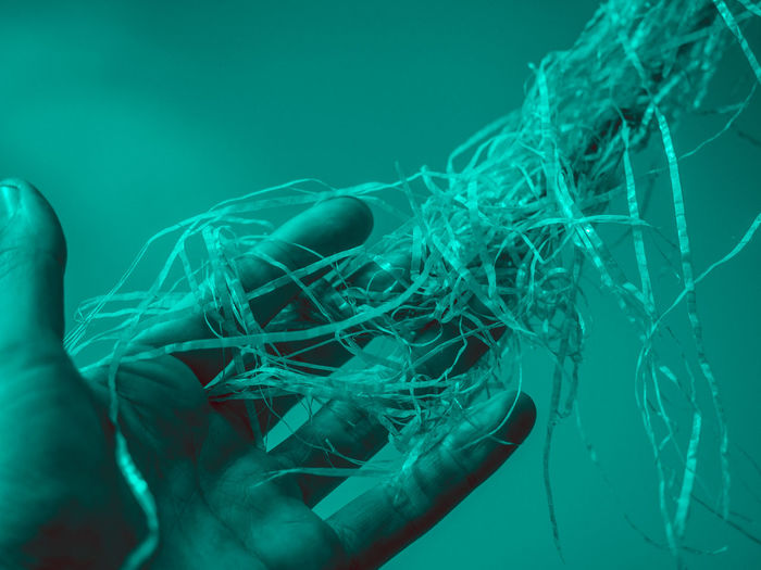 Indoors  Close-up Real People One Person Blue Complexity Human Body Part Tangled Motion Studio Shot Turquoise Colored Reaching Reaching Out Holding Human Hand Abstract Fiber Plastic Chaos Trapped Woven Surreal Twisted Wispy Intertwined Surrealism Mysterious