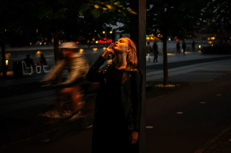 Woman Smoking Cigarette In City At Night