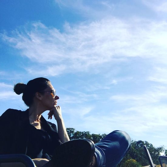 Low angle view of woman looking away sitting against sky