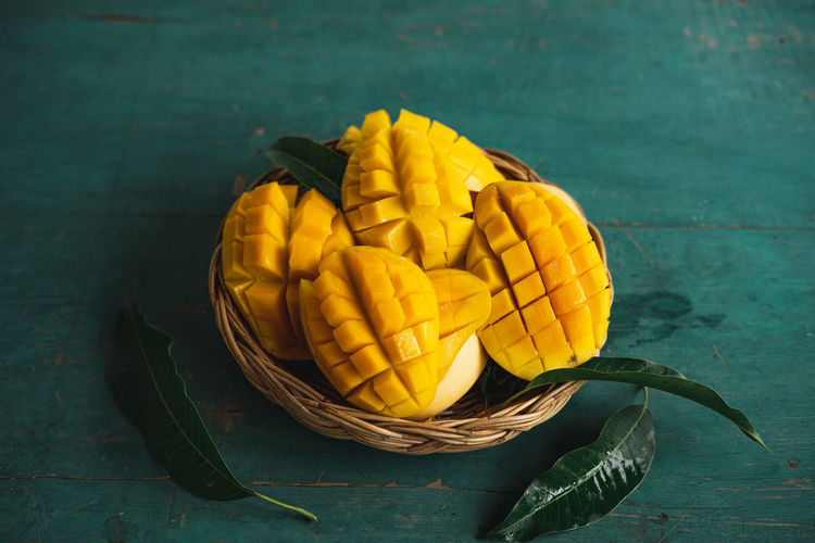 Mango in a basket on a green wood Food Food And Drink Healthy Eating Freshness Wellbeing Table Yellow Still Life Fruit Indoors  High Angle View No People Basket Container Wood - Material Close-up Vegetable Directly Above Bowl Ripe
