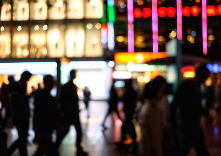 Defocused image of people on illuminated street at night