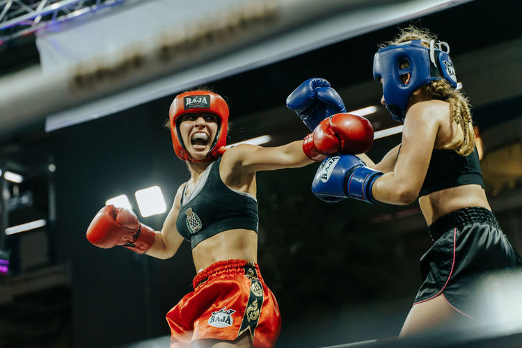 Young woman competing in a Muay Thai kickboxing fight in Bangkok, Thailand Boxing - Sport Sport Boxing Glove Two People Young Adult Competition Indoors  Strength Lifestyles Combat Sport Fighting Conflict Punching Athlete Adult People Anger Real People Sports Glove Aggression  MuayThai Muay Thai Aggression  Woman