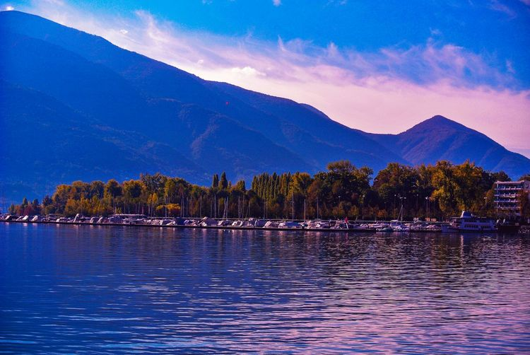 when the horizons color is your fave of the day! Switzerlandpictures Lugano, Switzerland Luganolake Tree Water Mountain Lake Sunset Blue Swan Mountain Peak Sky Landscape Horizon Over Water Harbor Boat Calm Pier Nautical Vessel Marina Dock Lakeshore