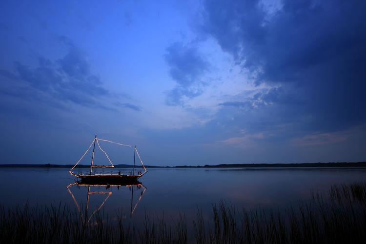 Illuminated sailing ship in sea against sky at dusk