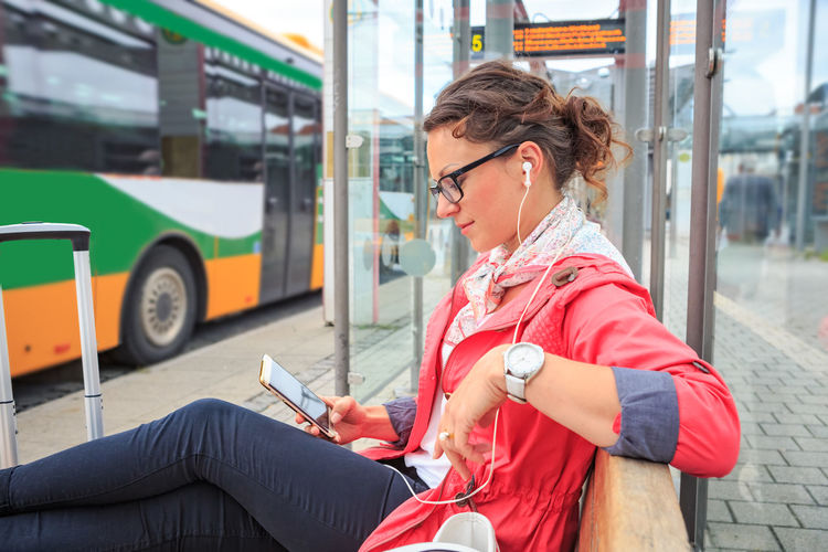 Woman Listening Music While Using Mobile Phone At Bus Stop