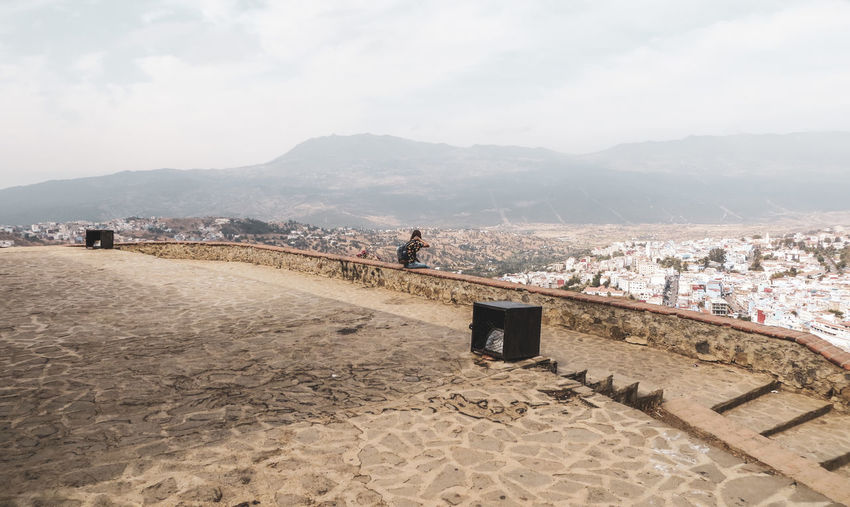 Woman sitting on retailing wall against town and mountains