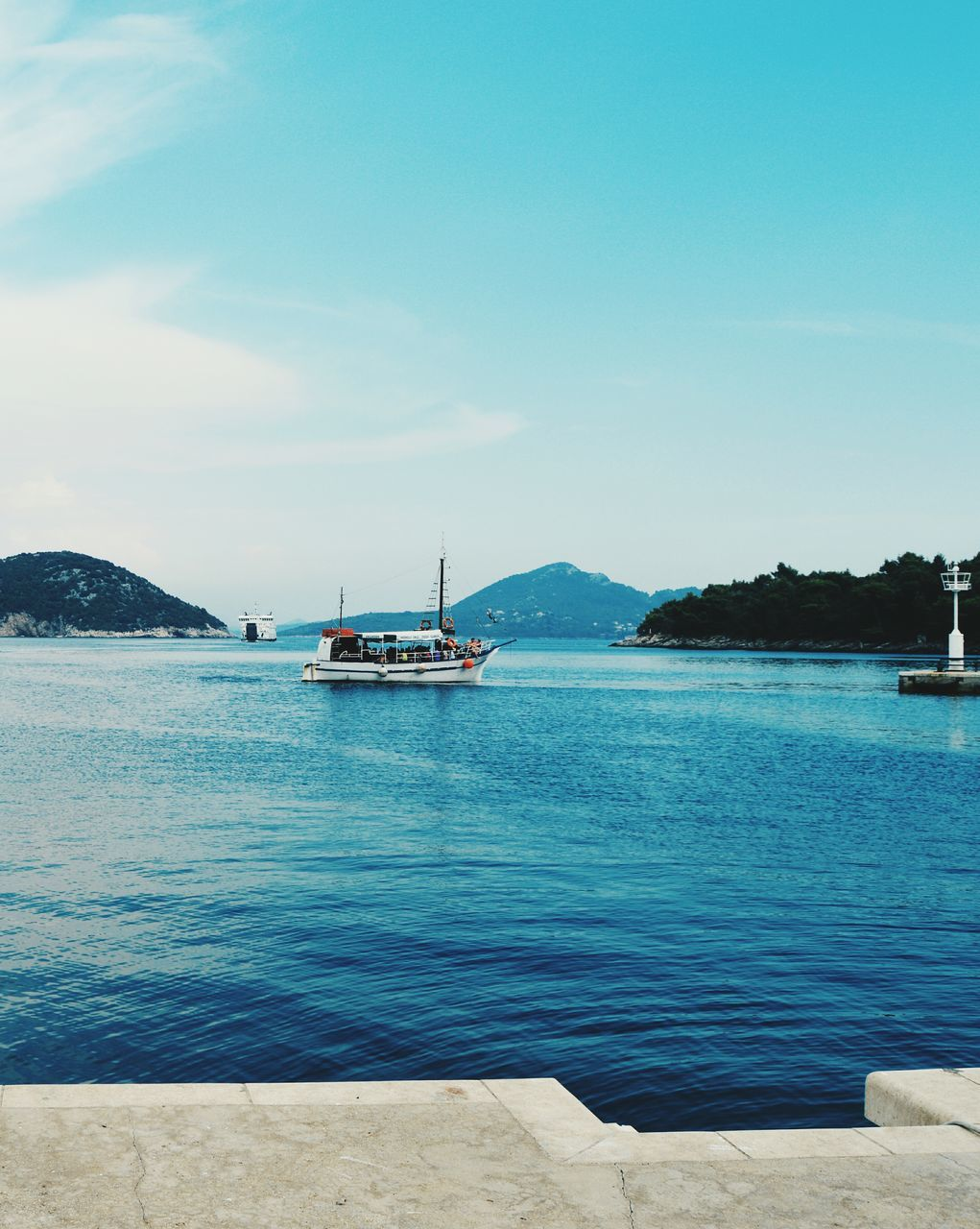 water, nautical vessel, sea, beauty in nature, nature, blue, transportation, scenics, mode of transport, sky, mountain, outdoors, tranquil scene, tranquility, day, travel destinations, cloud - sky, no people, sailboat, vacations, moored