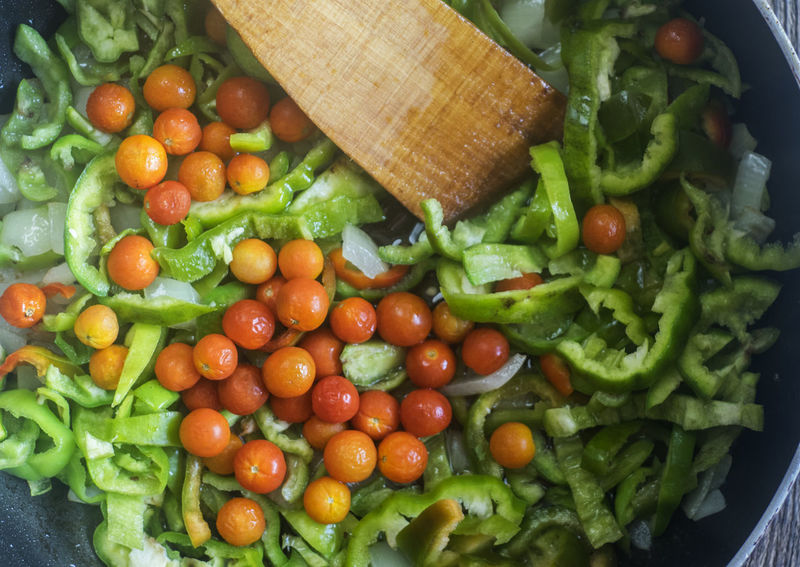 vegetable stew with bell pepper and cherry tomatoes in a frying pan on an old weathered wooden table Bell Cherry Frying Close-up Day Food Food And Drink Freshness Green Color Healthy Eating Indoors  No People Pan Pepper Stew Tomatoes Vegetable