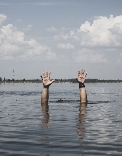 Cropped image of man drowning in sea