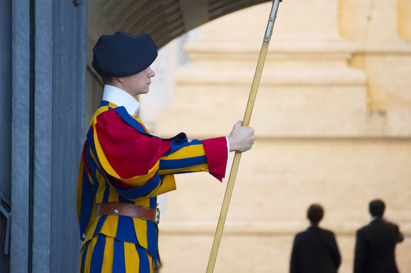 Side View Of A Guard Standing With A Stick