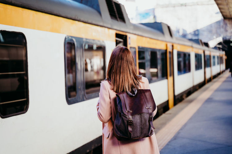 Rear view of woman on train at railroad station platform