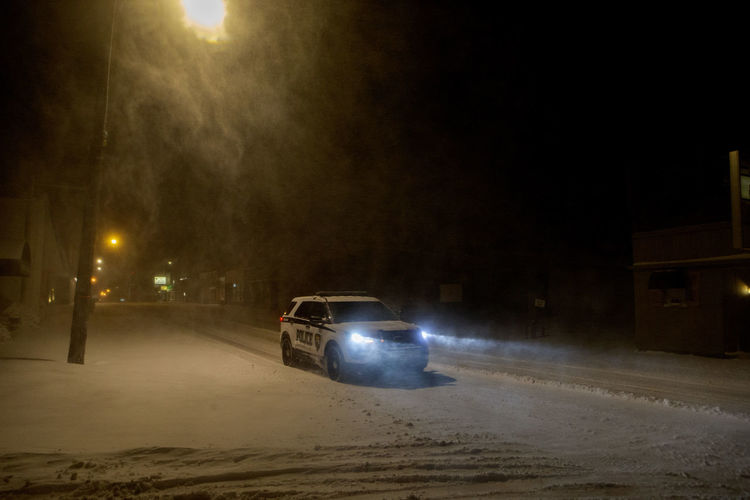 A Carterville Police Department squad car patrols downtown during the first major snow event of the year in southern Illinois. Interstate 57 was shut down by the Illinois Department of Transportation from Marion, Illinois to Mt. Vernon, Illinois because of gusty winds, drifting snow and ice. Night Illuminated Street Car Motor Vehicle City Transportation Mode Of Transportation Street Light Road Snow Land Vehicle Nature Winter Headlight Cold Temperature No People Snowing Dark Police Winter Ice Southern Illinois  Squad Car Wind
