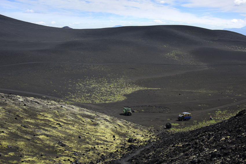 Trucks awaiting tourists in black volcanic desert Aerial View Beauty In Nature Day Far East Kamchatka Landscape Mountain Nature No People Outdoors Plant Russia Sky Sunset Yellow