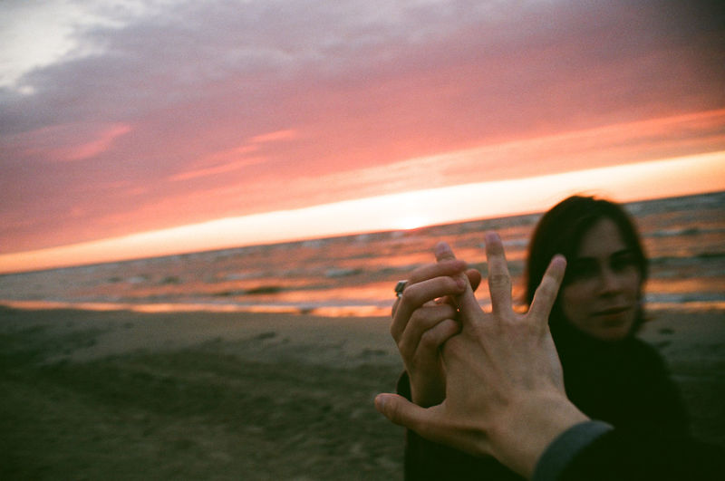 Woman holding man hand at beach against cloudy sky during sunset