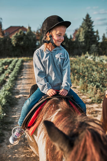 Little smiling girl learning horseback riding. 5-6 years old equestrian in helmet