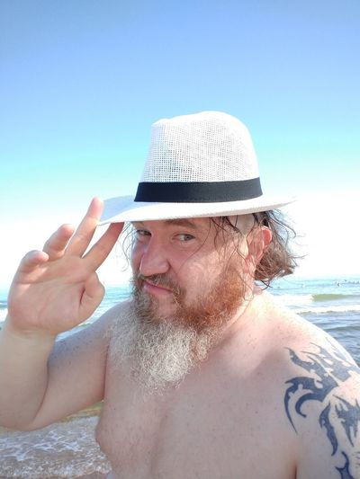 Portrait of shirtless man with hat on beach against sky