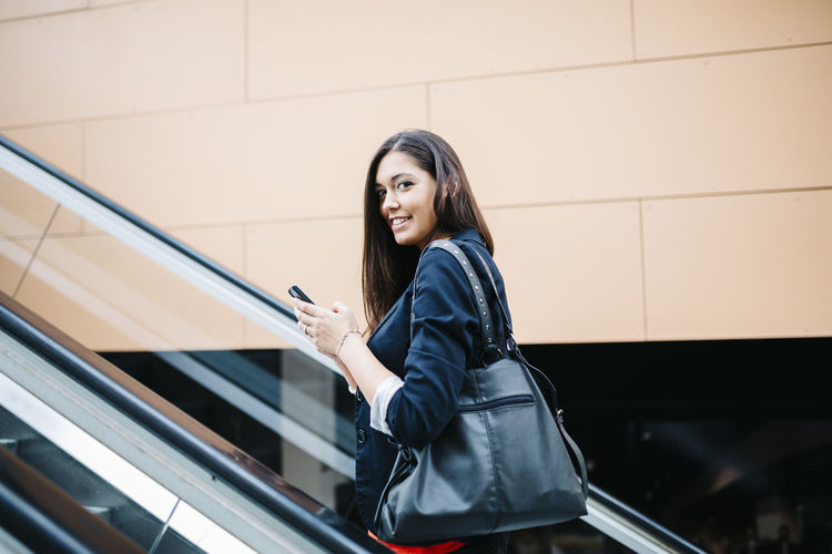 Young business woman using the smartphone when leaving work. Business Happy Woman Worker Bag Brunette Business Person Businesswoman Go Home Job Lifestyles Mechanic Stairs Mobile Office Building Outdoors Secretary Smart Phone Smiling Using Phone Young Adult