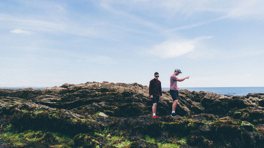 Side view of men walking on rocks against cloudy sky at looe during sunny day